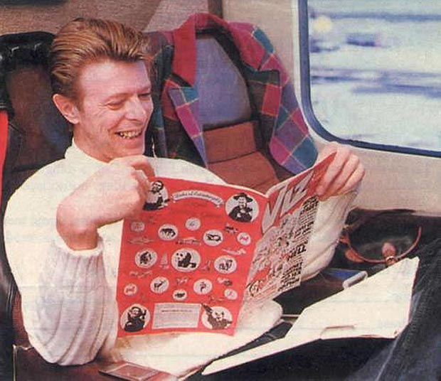 David Bowie, reading Viz on the train.